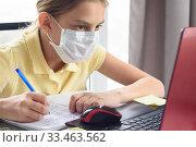 Девочка в защитной маске дистанционно смотри обучающие сервисы. Стоковое фото, фотограф Иванов Алексей / Фотобанк Лори