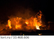 Купить «Burning fire flame on wooden house roof», фото № 33468606, снято 18 марта 2018 г. (c) Илья Андриянов / Фотобанк Лори