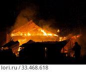 Firefighter at burning fire flame on wooden house roof. Стоковое фото, фотограф Илья Андриянов / Фотобанк Лори