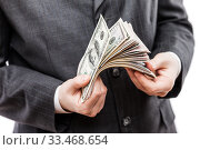 Businessman in black suit hand holding US dollar currency money. Стоковое фото, фотограф Илья Андриянов / Фотобанк Лори