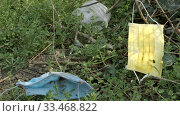 Купить «Close-up of used medical disposable face masks and plastic bags on the branches of trees. Face masks and plastic debris polluting urban parks since Coronavirus (COVID-19). Ecological pollution problem», видеоролик № 33468822, снято 26 марта 2019 г. (c) Некрасов Андрей / Фотобанк Лори