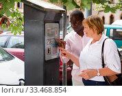 Polite intelligent African man helping middle aged woman to buy ticket in parking meter on summer city street. Стоковое фото, фотограф Яков Филимонов / Фотобанк Лори