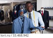 Купить «Fashion designer is creating business image in men's store», фото № 33468942, снято 24 мая 2020 г. (c) Яков Филимонов / Фотобанк Лори