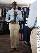 Купить «Portrait of male client choosing classic beige jacket in the mall», фото № 33468954, снято 7 апреля 2020 г. (c) Яков Филимонов / Фотобанк Лори
