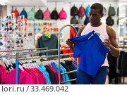 Portrait of African American man choosing shorts in sporting goo. Стоковое фото, фотограф Яков Филимонов / Фотобанк Лори