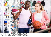 European woman and Afro man choosing sneakers in sporting goods. Стоковое фото, фотограф Яков Филимонов / Фотобанк Лори