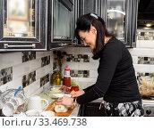 Купить «Немолодая женщина готовит еду на кухне», эксклюзивное фото № 33469738, снято 9 марта 2020 г. (c) Игорь Низов / Фотобанк Лори
