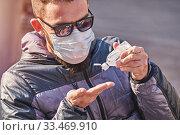 Man wearing mask uses antibacterial gel on hands. Стоковое фото, фотограф Kira_Yan / Фотобанк Лори