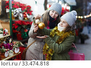 Woman and her daughter are preparing for Christmas and choosing balls on the tree. Стоковое фото, фотограф Яков Филимонов / Фотобанк Лори
