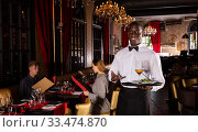 Polite waiter holding tray in restaurant with customers behind him. Стоковое фото, фотограф Яков Филимонов / Фотобанк Лори