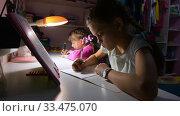 Купить «Две девочки делаю уроки поздно вечером, при свете настольной лампы», видеоролик № 33475070, снято 25 марта 2020 г. (c) Иванов Алексей / Фотобанк Лори