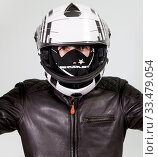 Купить «Portrait of motorcyclist rider wearing crash helmet, dust facial mask, leather brown jacket, a grey background, looking at camera», фото № 33479054, снято 26 марта 2020 г. (c) Кекяляйнен Андрей / Фотобанк Лори