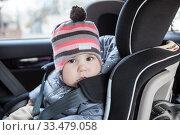 Portrait of Caucasian infant child sitting in car safety seat, eight month old. Стоковое фото, фотограф Кекяляйнен Андрей / Фотобанк Лори