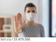 Купить «woman in protective medical mask making stop sign», фото № 33479566, снято 13 марта 2020 г. (c) Syda Productions / Фотобанк Лори