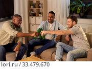 Купить «happy male friends drinking beer at home at night», фото № 33479670, снято 28 декабря 2019 г. (c) Syda Productions / Фотобанк Лори