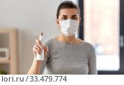 Купить «close up of woman in mask holding hand sanitizer», фото № 33479774, снято 13 марта 2020 г. (c) Syda Productions / Фотобанк Лори