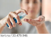 close up of woman spraying hand sanitizer. Стоковое фото, фотограф Syda Productions / Фотобанк Лори