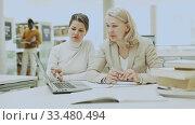 Female teacher working with girl student in university library. Стоковое видео, видеограф Яков Филимонов / Фотобанк Лори