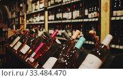 Купить «Rack shelves with wine bottles in wine store. Nameplates in Catalan with name of Spanish wine regions», видеоролик № 33484470, снято 19 февраля 2020 г. (c) Яков Филимонов / Фотобанк Лори
