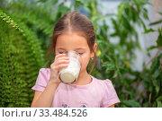Купить «Girl drinks kefir from a transparent glass at home. Proper nutrition for the baby», фото № 33484526, снято 1 апреля 2020 г. (c) Екатерина Кузнецова / Фотобанк Лори