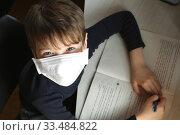 Child with antiviral mask doing his homework in quarantine. Стоковое фото, фотограф Попова Ольга / Фотобанк Лори