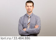 Купить «A worker in a cage shirt and tie crossed his hands on his chest. half-length portrait», фото № 33484886, снято 4 апреля 2020 г. (c) Владимир Арсентьев / Фотобанк Лори