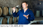 Male keeping ageing process of wine. Стоковое фото, фотограф Яков Филимонов / Фотобанк Лори