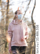 Купить «Portrait of caucasian sporty woman wearing medical protection face mask while walking in park, relaxing and listening to music. Corona virus, or Covid-19, is spreading all over the world», фото № 33486558, снято 28 марта 2020 г. (c) Matej Kastelic / Фотобанк Лори