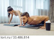 Morning fitness training of family couple at home. Стоковое фото, фотограф Tryapitsyn Sergiy / Фотобанк Лори