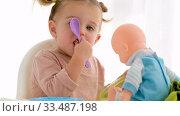 Little girl sharing food with doll. Стоковое видео, видеограф Ekaterina Demidova / Фотобанк Лори