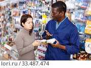 Competent seller consulting young woman about purchase of supplies for household works in store. Стоковое фото, фотограф Яков Филимонов / Фотобанк Лори
