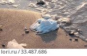 Купить «Close-up of face masks and plastic debris on the beath in surf zone. Coronavirus COVID-19 is contributing to pollution, as discarded used masks clutter polluting urban beaches along with plastic trash», видеоролик № 33487686, снято 5 апреля 2020 г. (c) Некрасов Андрей / Фотобанк Лори