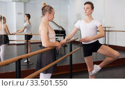 Купить «Choreographer helping young man dancer to have right position. Exercising at the barre by the mirror», фото № 33501550, снято 26 апреля 2019 г. (c) Яков Филимонов / Фотобанк Лори