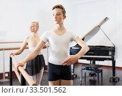 Купить «Choreographer woman and young man do exercises at ballet bar in hall with mirror», фото № 33501562, снято 26 апреля 2019 г. (c) Яков Филимонов / Фотобанк Лори