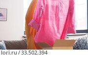 Купить «happy asian young woman with parcel box at home», видеоролик № 33502394, снято 26 марта 2020 г. (c) Syda Productions / Фотобанк Лори