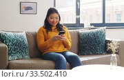 Купить «smiling asian woman with smartphone at home», видеоролик № 33502410, снято 26 марта 2020 г. (c) Syda Productions / Фотобанк Лори