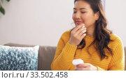 Купить «asian woman with earphones and smartphone at home», видеоролик № 33502458, снято 30 марта 2020 г. (c) Syda Productions / Фотобанк Лори