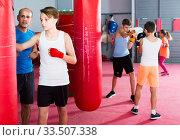 Купить «Boxing coach closely follows the work of the pupil on the punching bag», фото № 33507338, снято 12 апреля 2017 г. (c) Яков Филимонов / Фотобанк Лори