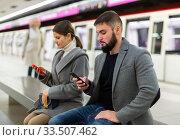 Купить «Young man and brunette with phones on bench in subway station», фото № 33507462, снято 9 апреля 2020 г. (c) Яков Филимонов / Фотобанк Лори
