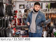 Купить «Buyer chooses frying pan in the hardware store», фото № 33507498, снято 28 января 2020 г. (c) Яков Филимонов / Фотобанк Лори