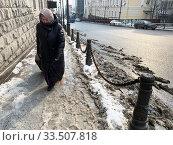 Пожилая женщина с чемоданом идет по тротуару на Океанском проспекте в феврале. Россия, город Владивосток. Редакционное фото, фотограф Овчинникова Ирина / Фотобанк Лори