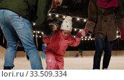 Купить «happy family at outdoor skating rink in winter», видеоролик № 33509334, снято 22 марта 2020 г. (c) Syda Productions / Фотобанк Лори