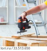 Young man assembling wood pallet. Стоковое фото, фотограф Elnur / Фотобанк Лори