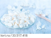Купить «Meringue cookies on plate and on a table», фото № 33517418, снято 9 апреля 2020 г. (c) age Fotostock / Фотобанк Лори