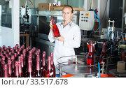 young woman holding newly produced bottles of wine. Стоковое фото, фотограф Яков Филимонов / Фотобанк Лори