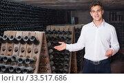 Male wine maker showing bottles on winery. Стоковое фото, фотограф Яков Филимонов / Фотобанк Лори