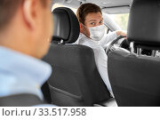 taxi driver in face protective mask driving car. Стоковое фото, фотограф Syda Productions / Фотобанк Лори