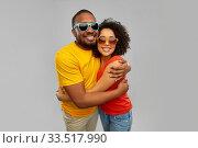 happy african couple in sunglasses hugging. Стоковое фото, фотограф Syda Productions / Фотобанк Лори