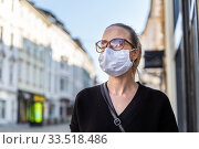 Купить «COVID-19 pandemic coronavirus. Young girl in city street wearing face mask protective for spreading of coronavirus disease 2020. Close up of young woman with medical mask on face against SARS-CoV-2», фото № 33518486, снято 8 апреля 2020 г. (c) Matej Kastelic / Фотобанк Лори