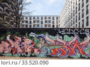 Купить «Remains of a property wall with graffiti in front of a new residential building on the former wall strip at the East Side Gallery in Berlin-Friedrichshain», фото № 33520090, снято 4 апреля 2019 г. (c) Caro Photoagency / Фотобанк Лори